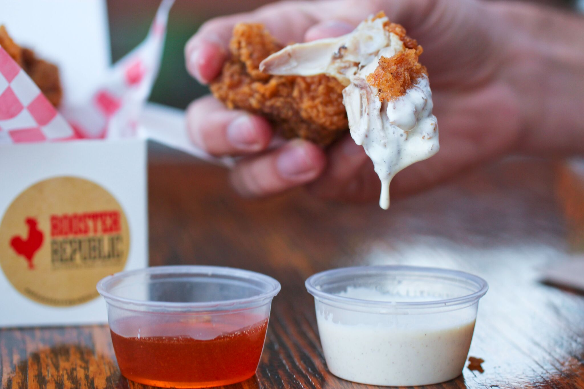 Rooster Republic's fried chicken takes a dip in their house-made white BBQ sauce | photo courtesy of Rooster Republic