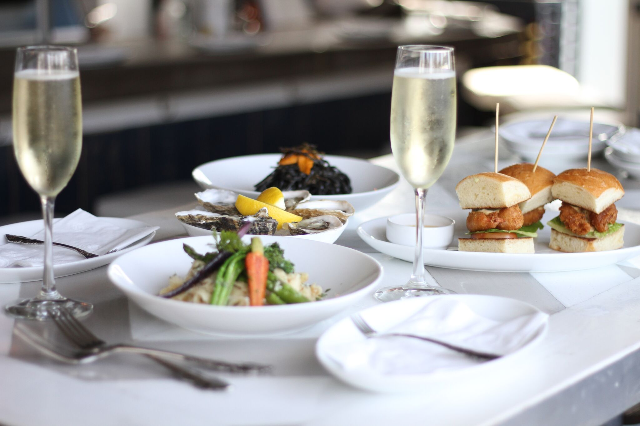 A varietal spread of Shuck Oyster Bar's seafood offerings, complete with bubbly