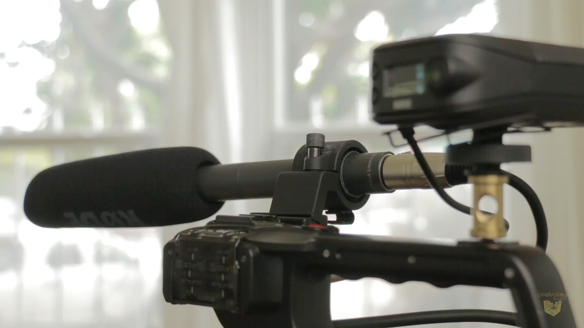 A Rode shotgun mic and Rodelink wireless lav mic receiver attached to the top of our Canon C100.