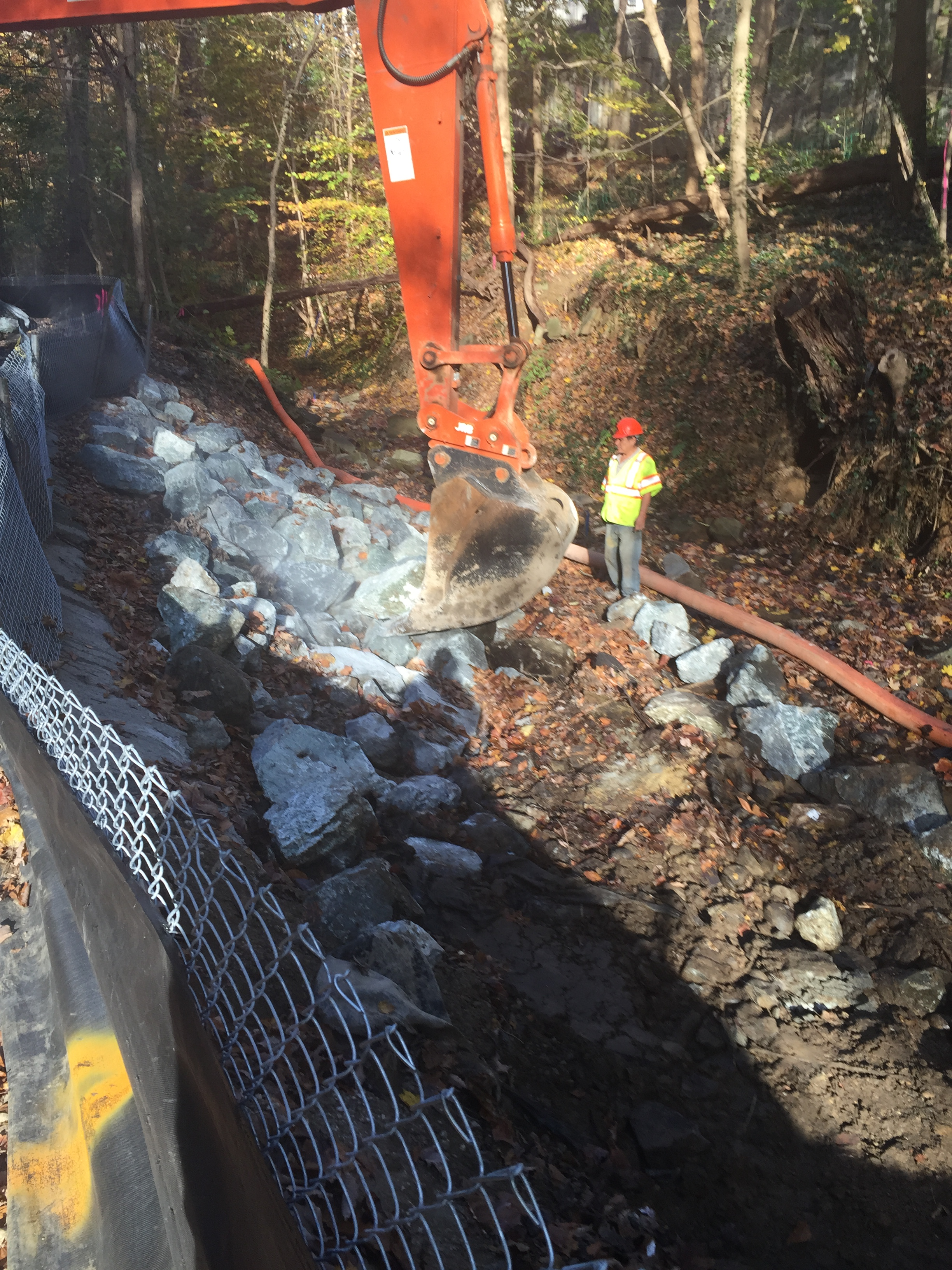 Excavating the existing stream bank to reach the retaining wall subgrade