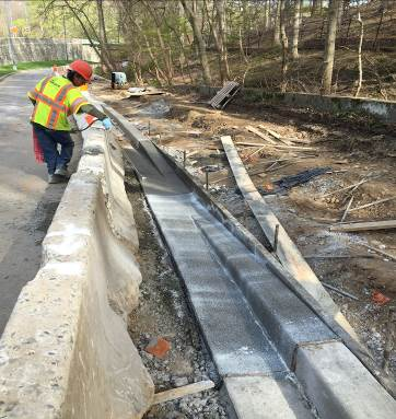 Placing curing compound on freshly poured concrete at a wheelchair/bicycle ramp location