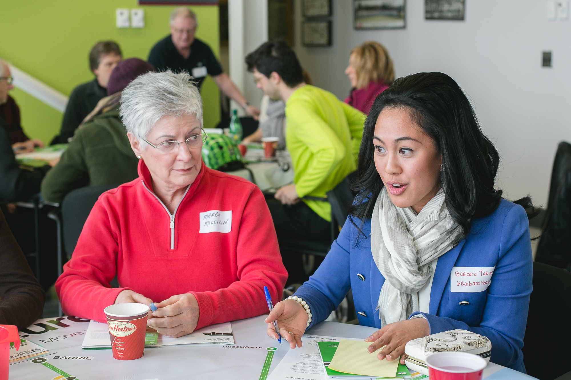 Two participants at the Public Roundtable meetings discuss transit priorities