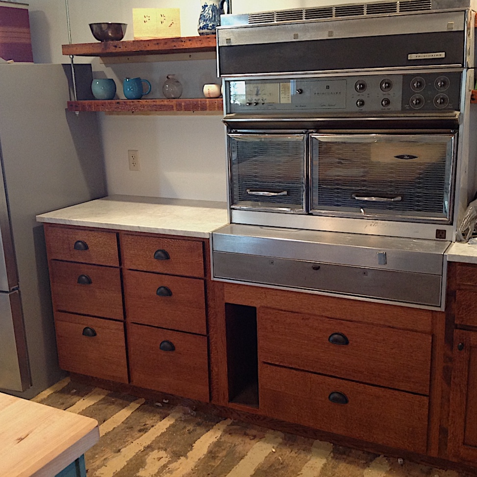 "Another view of some of the wood . . . notice the reclaimed shelving and original Depot floor mixed with the new quarter-sawn oak cabinets and Maple ""butcher block"" counter top in the foreground. Oh, yeah, then there is the Flair stove . . . made in 1964 by General Motors. But that's another story!"