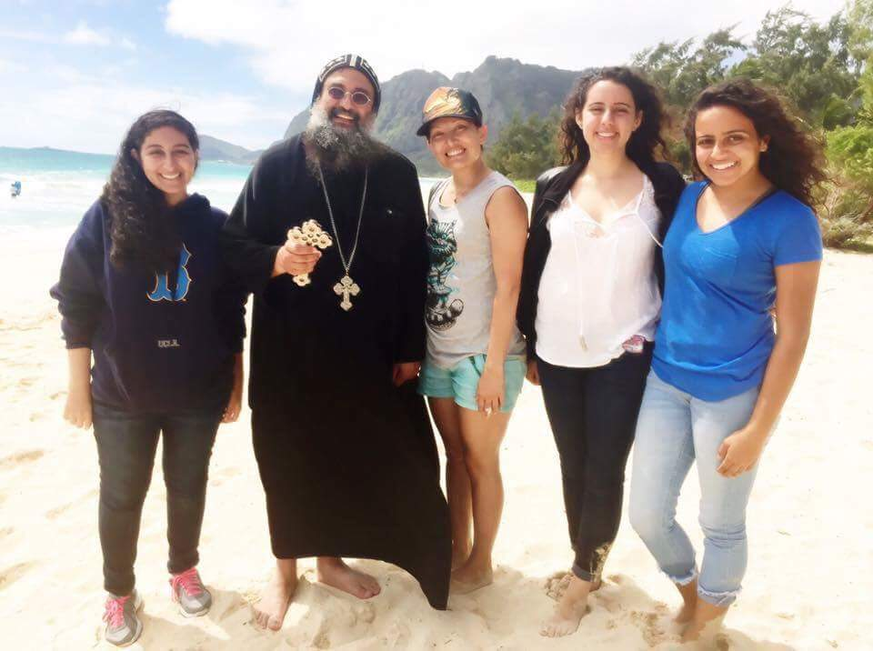 """""""Went for a walk and found God. Father Anastasi and 3 beautiful young ladies visiting Hawaii as part of a Coptic Christian mission trip to Hawaii. I had never heard of Coptic before so this was enlightening for me. So interesting with the background being Egyptian! They were with a larger group reading prayer on the beach and we were curious about them so we just went up and struck up conversation. They were so welcoming and it was a very unplanned and enjoyable time getting to know them and hear their story and more about their faith. What was so cool was how comfortable I felt spending time with them. Thank you for a wonderful morning! Love and Aloha! 🌺"""" -Nicole Parsons"""