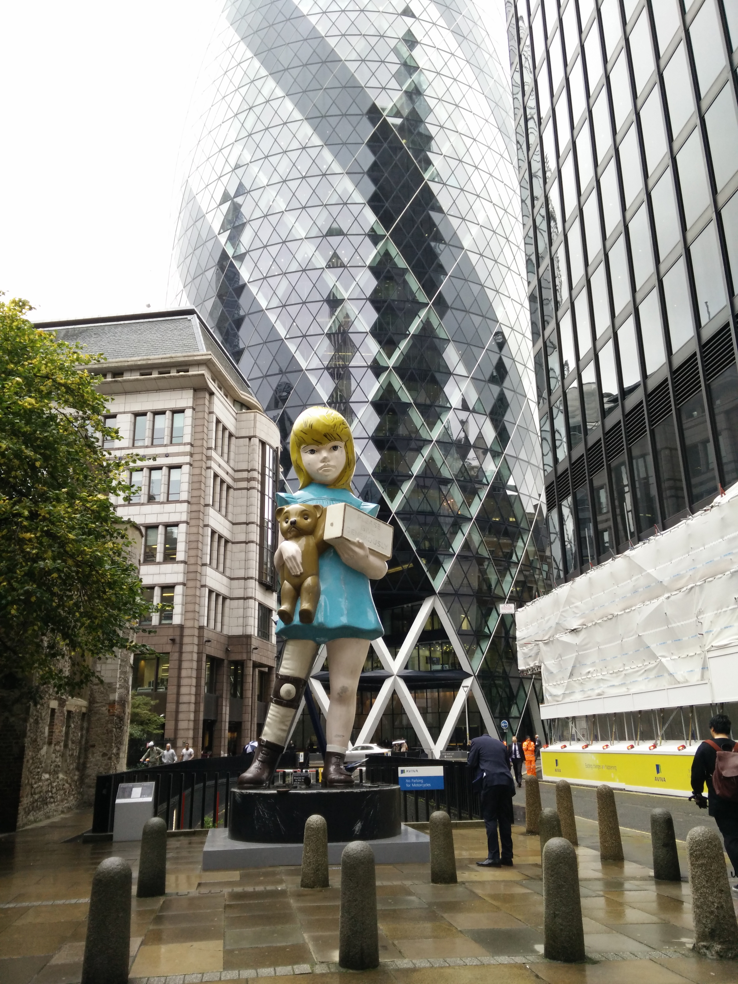 Damien Hirst's Charity  works great against the background of the business district.