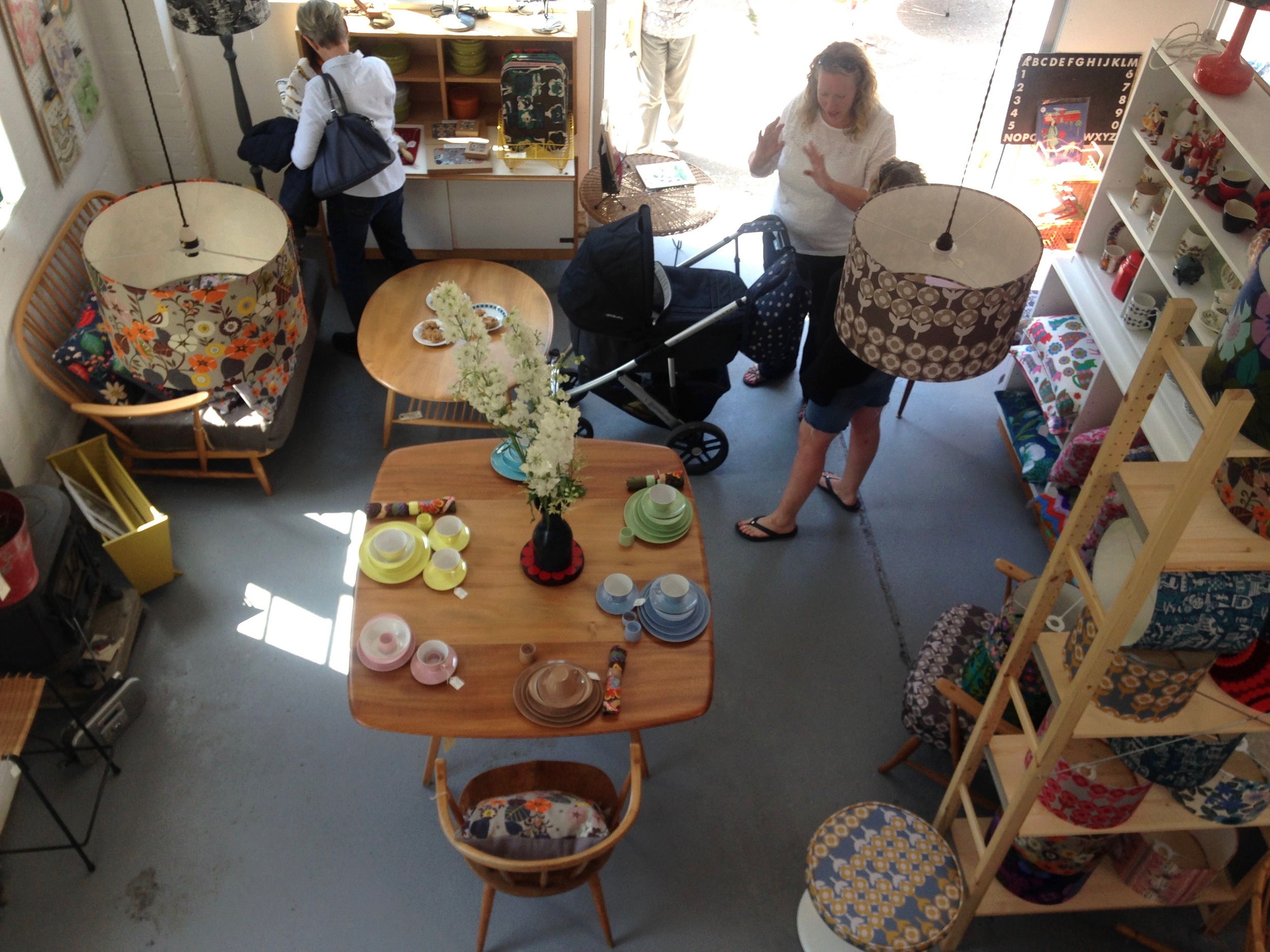 An overhead shot of lampshades and the Ercol dining table, this is taken from the mezzanine where lots of packaging and items waiting to be reupholstered are stored.