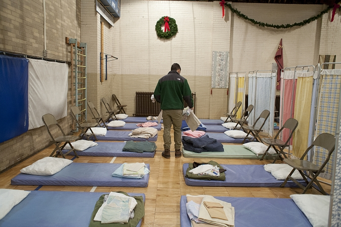 A volunteer prepares beds for the guests of Housing Forward.