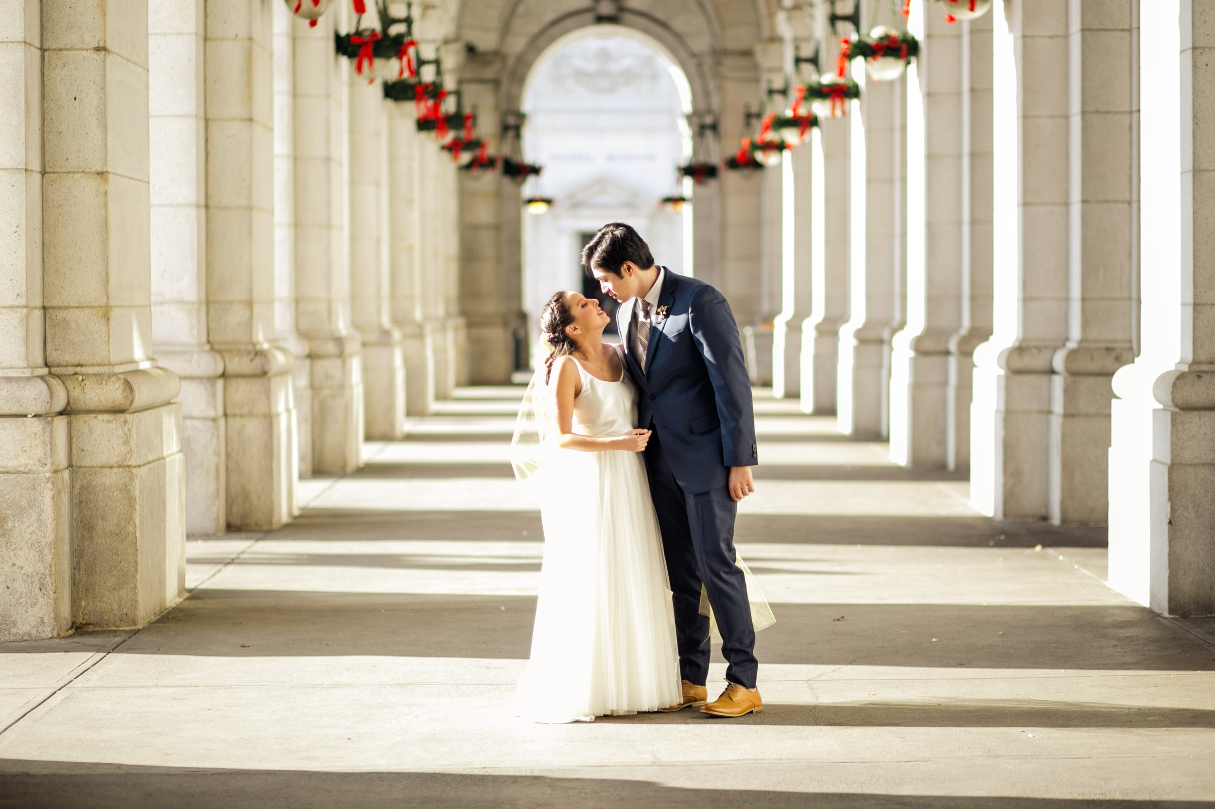 The bride and groom sharing a kiss at Union Station before their wedding in downtown DC and reception at a brewery.