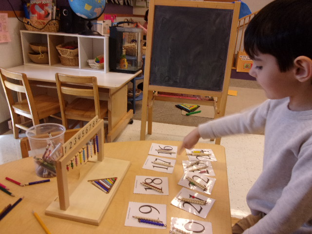 Aaron matching bead bars to numbers on the bead bar row and number cards.