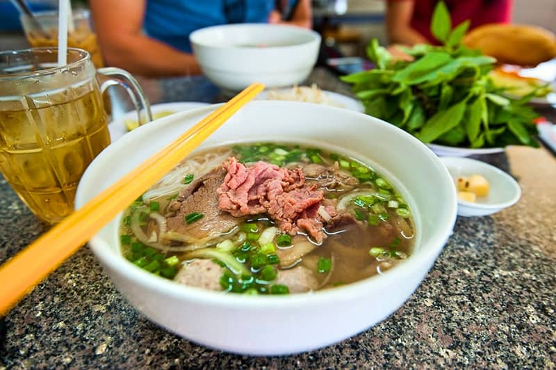 Pho -   Cost $2 - $4 -    Phở or pho is a Vietnamese noodle soup consisting of broth, rice noodles called bánh phở, a few herbs, and meat, primarily made with either beef or chicken.