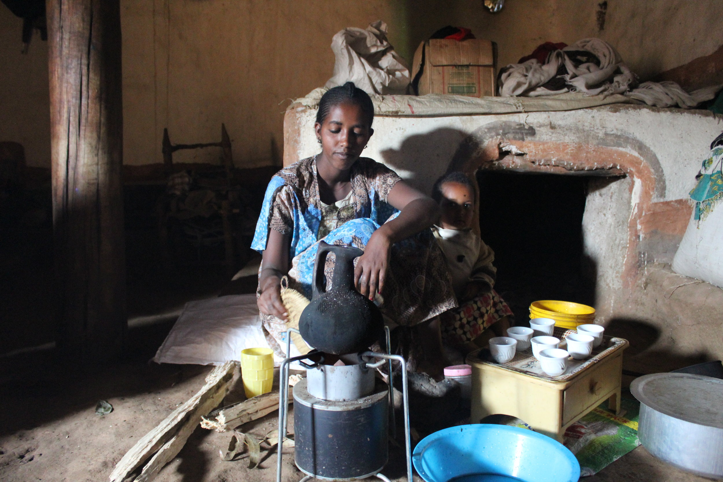 Ethiopian woman making coffee on the EzyStove. I love her little girl peeking out from behind her elbow.