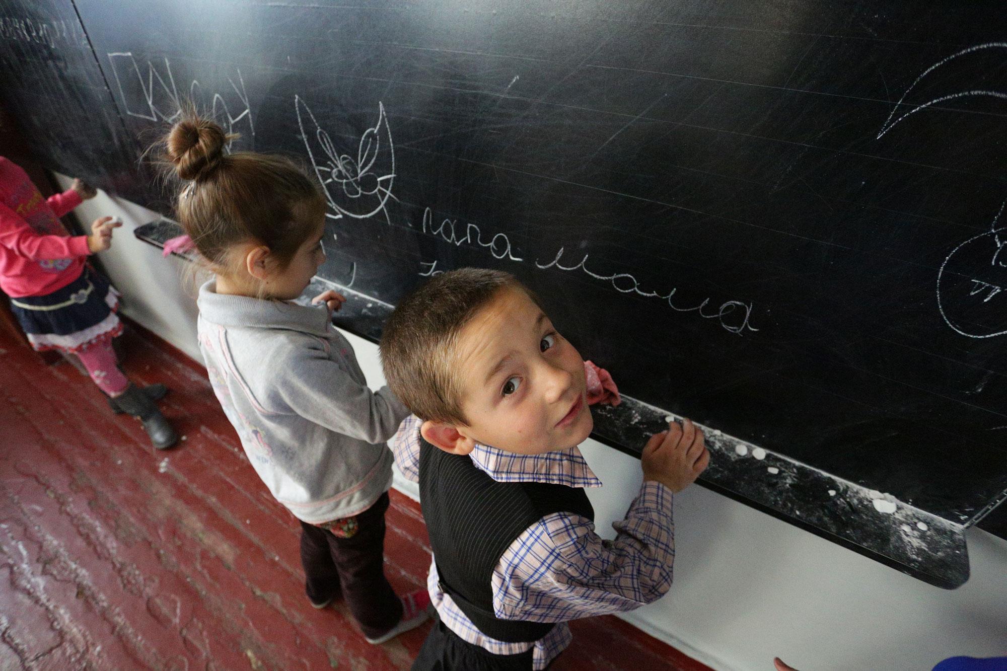 Des enfants écrivent au tableau dans une école du village de Staromykhailovka, sur la ligne de front, entre les villes de Donetsk et Mariyanovka, en Ukraine. © UNICEF / Aleksey Filippov