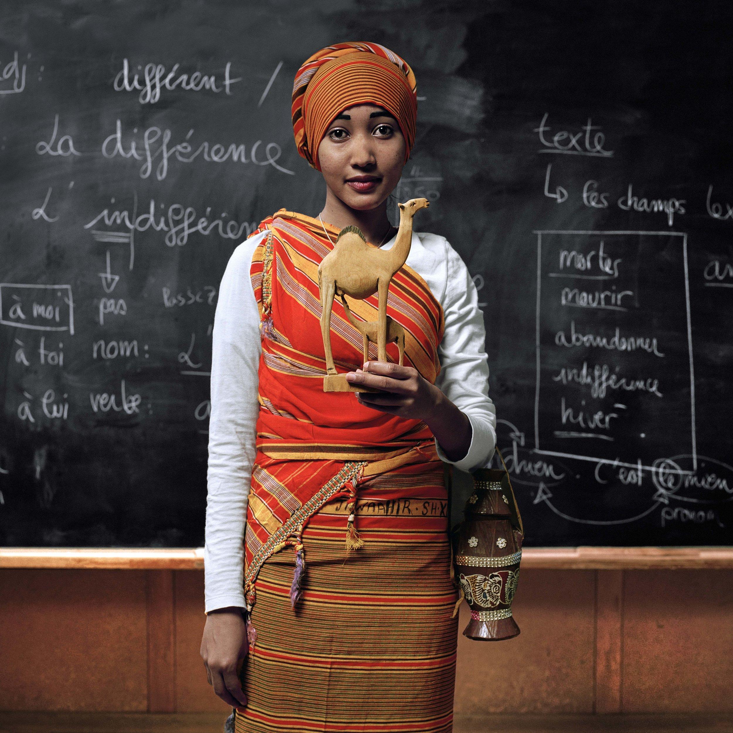 Samira , Somalie: «  Les habits que je porte sont traditionnels de mon pays et représentent ma culture. Quand je mets ces habits, c'est pour des événements importants. Comme pour un mariage ou une fête. Quand un homme se marie avec une femme, elle doit obligatoirement porter ces habits. Et l'homme doit donner 100 dromadaires à la famille de la mariée. Dans mon pays, les dromadaires sont très importants et on boit aussi son lait. Ce sont les plus beaux du monde et les animaux les plus nombreux de Somalie. C'est pourquoi j'ai choisi une statuette qui les représente .» ©Vivian Olmi