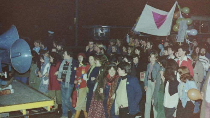 The 1979 parade was incident free, despite a large police presence. Notice the pink triangle banner is carried in this picture.