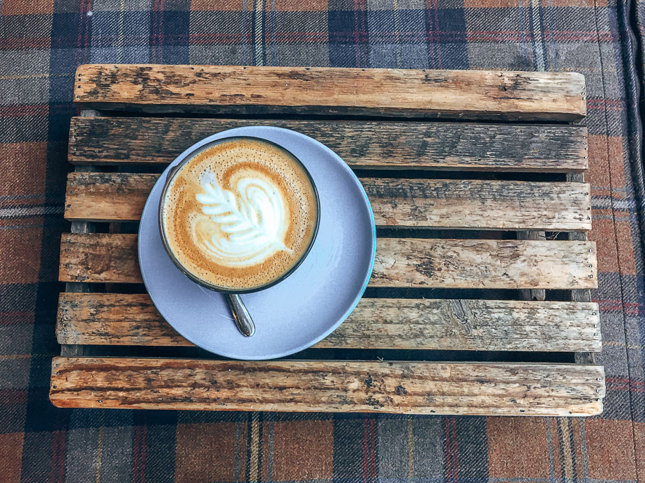 A-latte-served-on-a-wooden-tray-at-The-Milkman-Edinburgh-Scotland.jpg