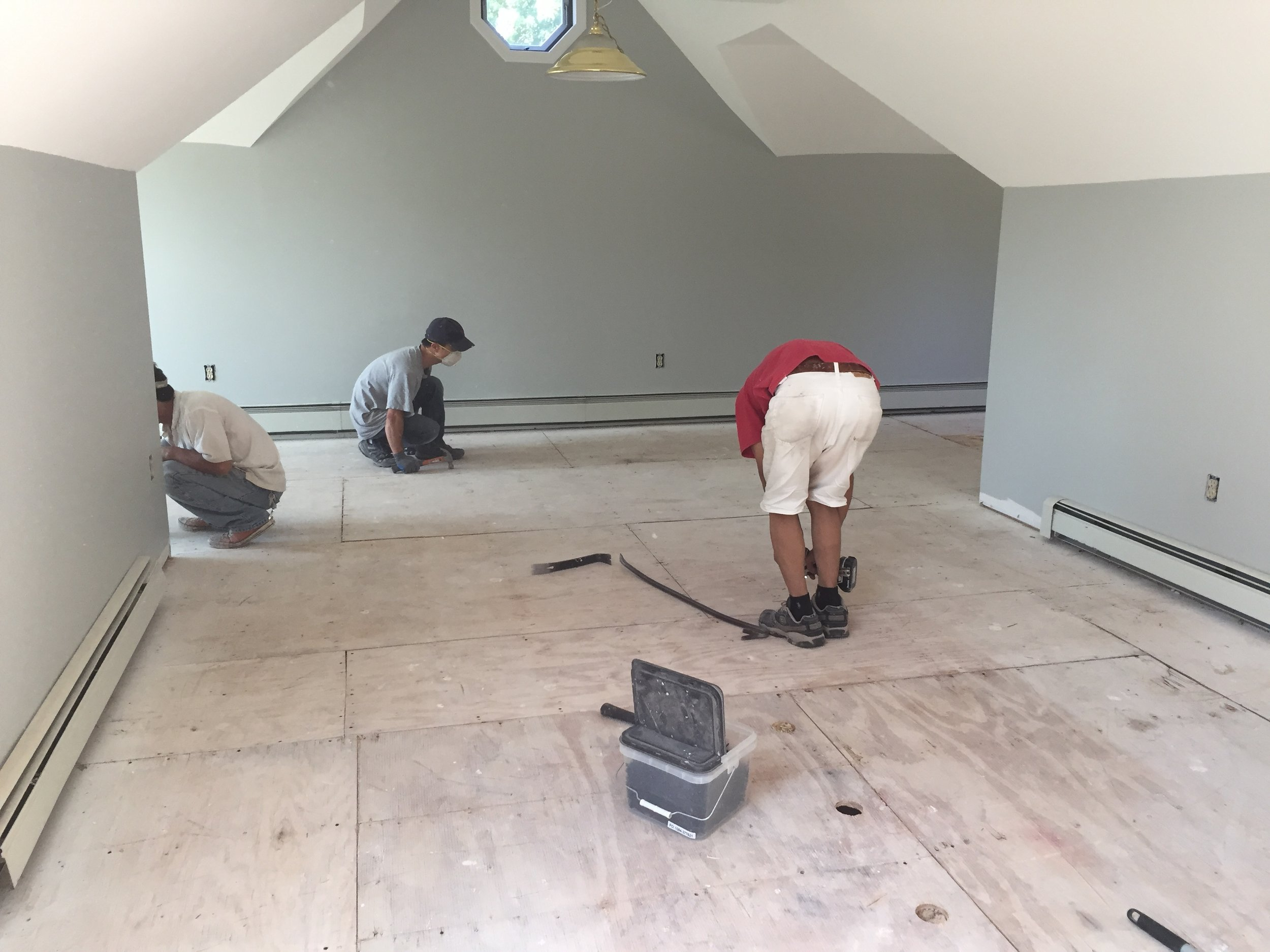 PROGRESS - TV room with carpeting removed + screwing the subfloor to the floor joists to eliminate squeaking