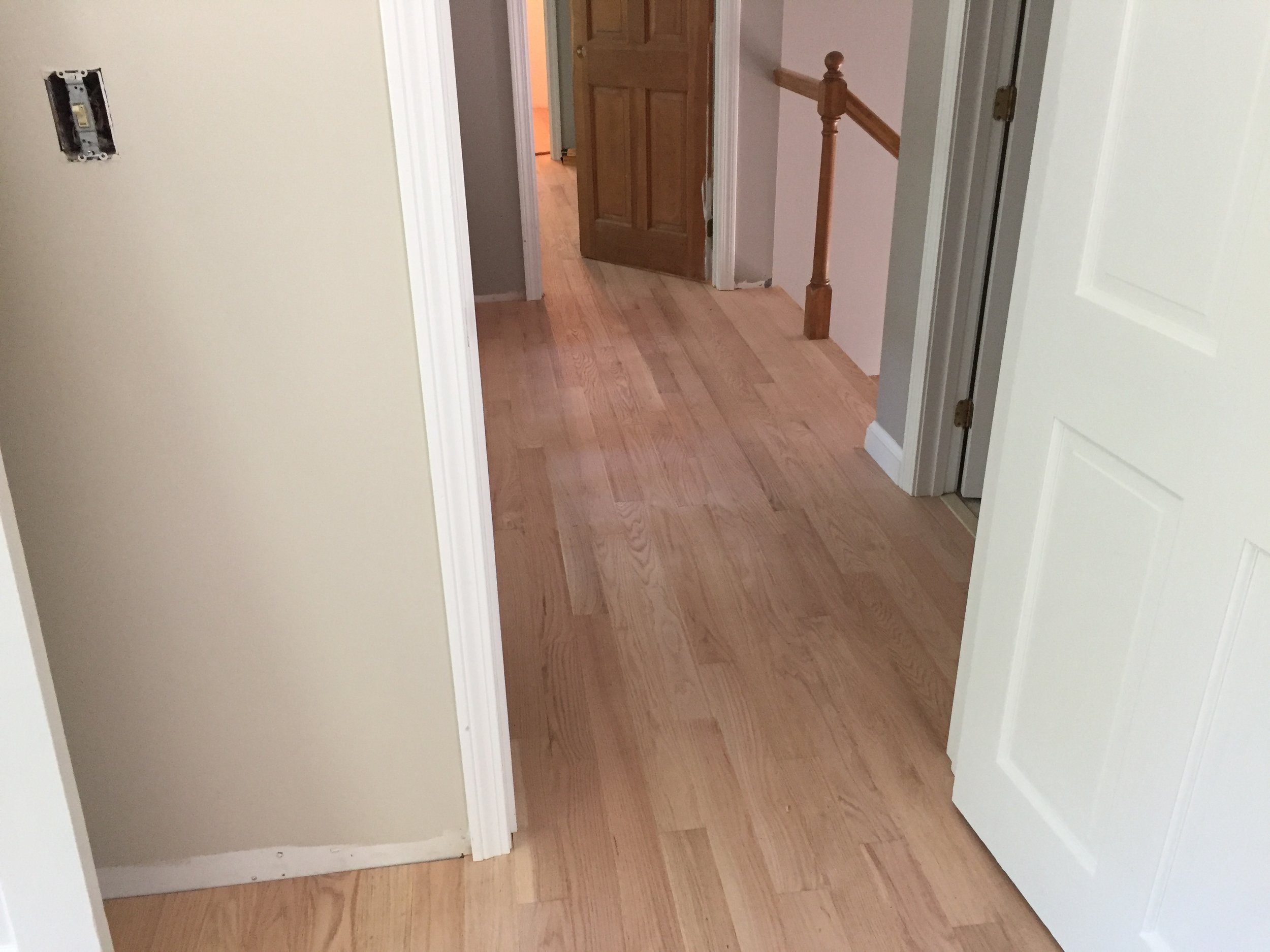 AFTER - hall with new red oak flooring installed (unstained)