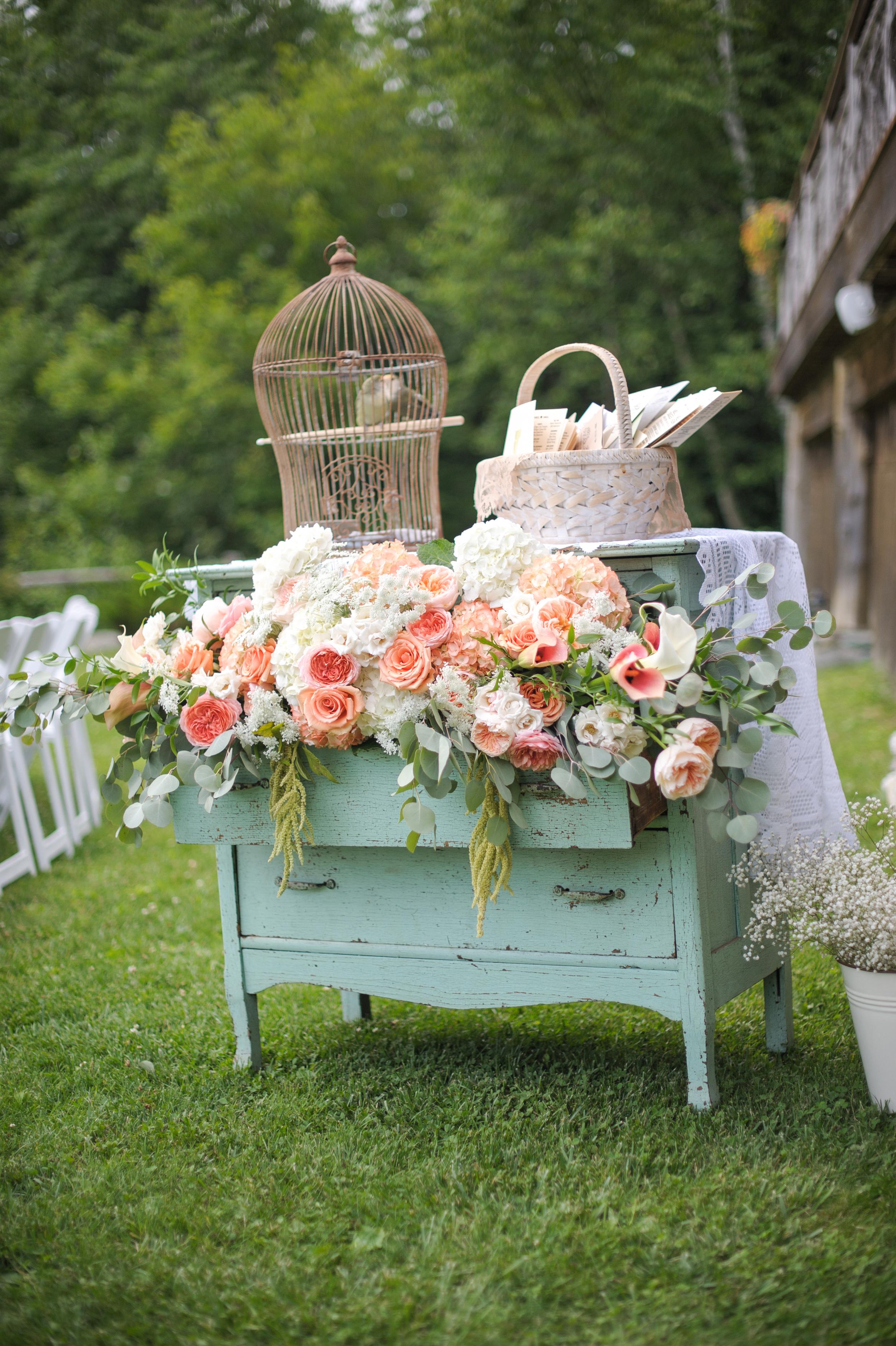 vintage_dresser_and_birdcage_filled_with_flowers_for_wedding