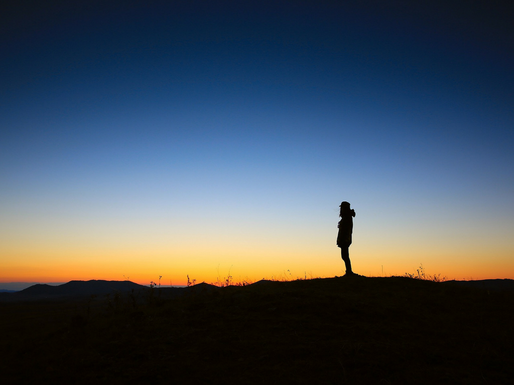 A lone silhouetted person stands against a sunset.