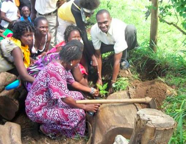 Geofrey, in white, helps the graduating clients to plant a celebratory tree