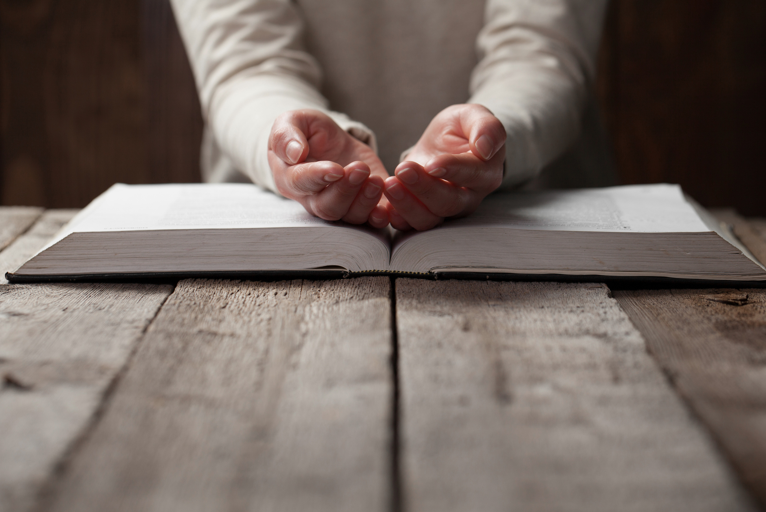 Praying hands resting on book