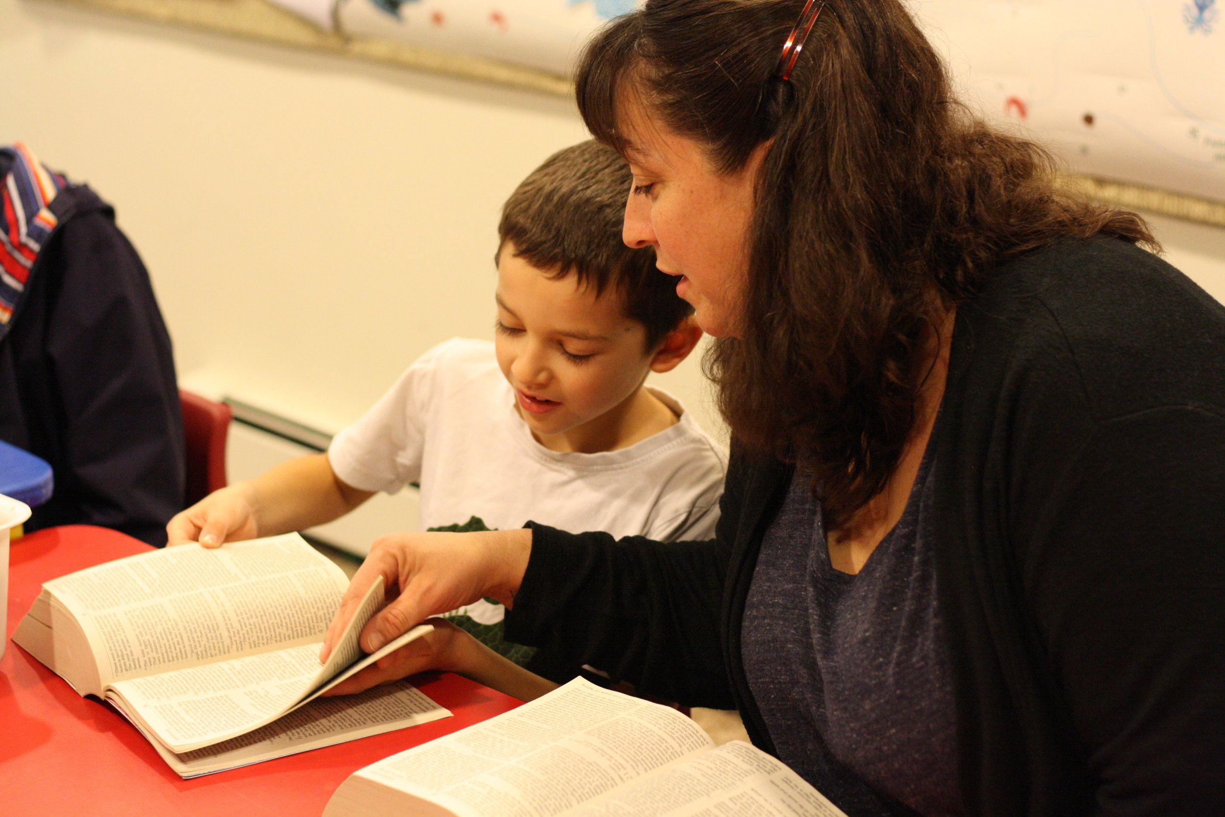 Teacher assists student to find Bible passage