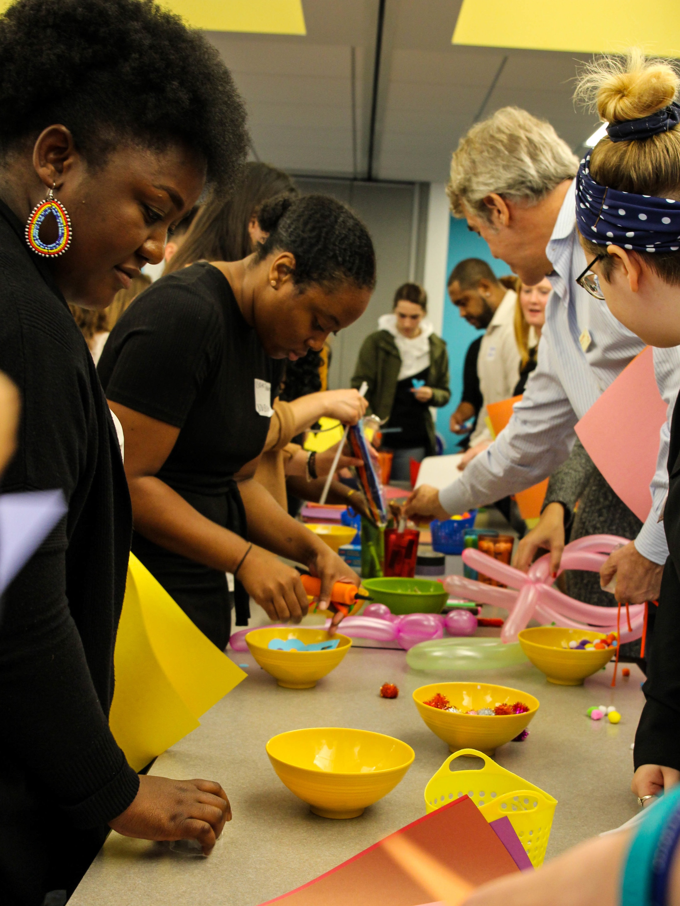 students doing an activity with craft supplies at a table