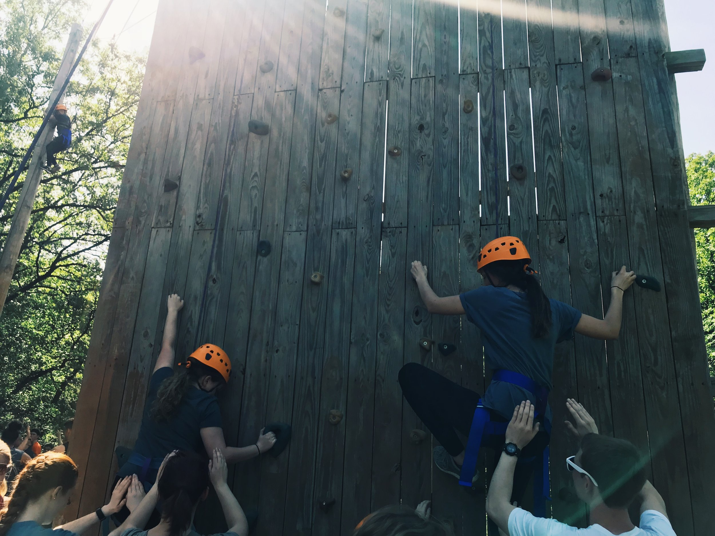 Missionaries climb the rock wall, supported and spotted by their team members and leaders.
