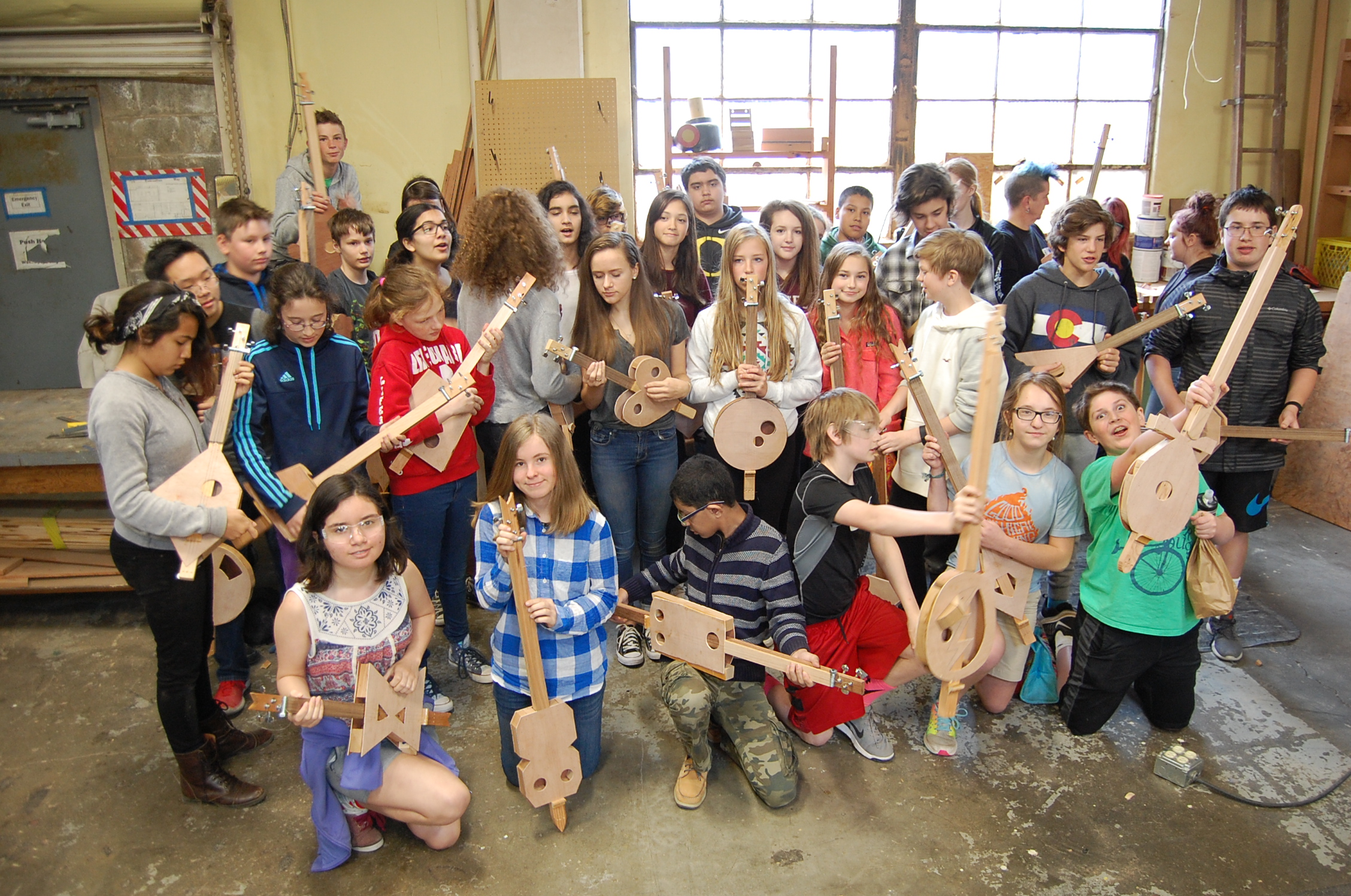 7th grade class posing with their new 3-string instruments