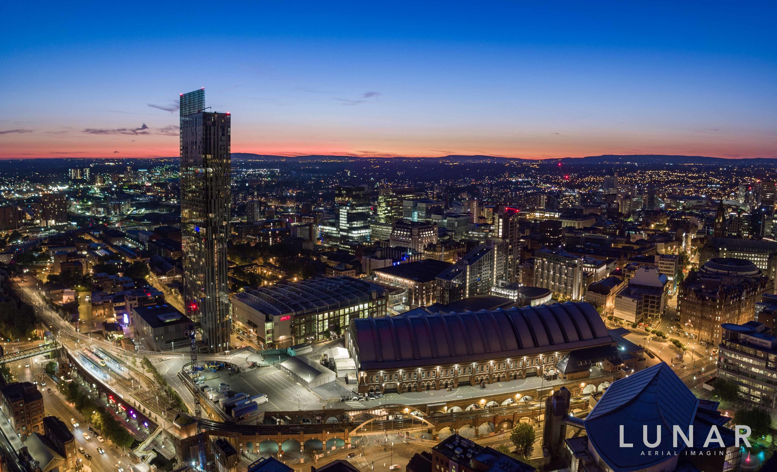 Aerial photo of Manchester at dusk with city lights