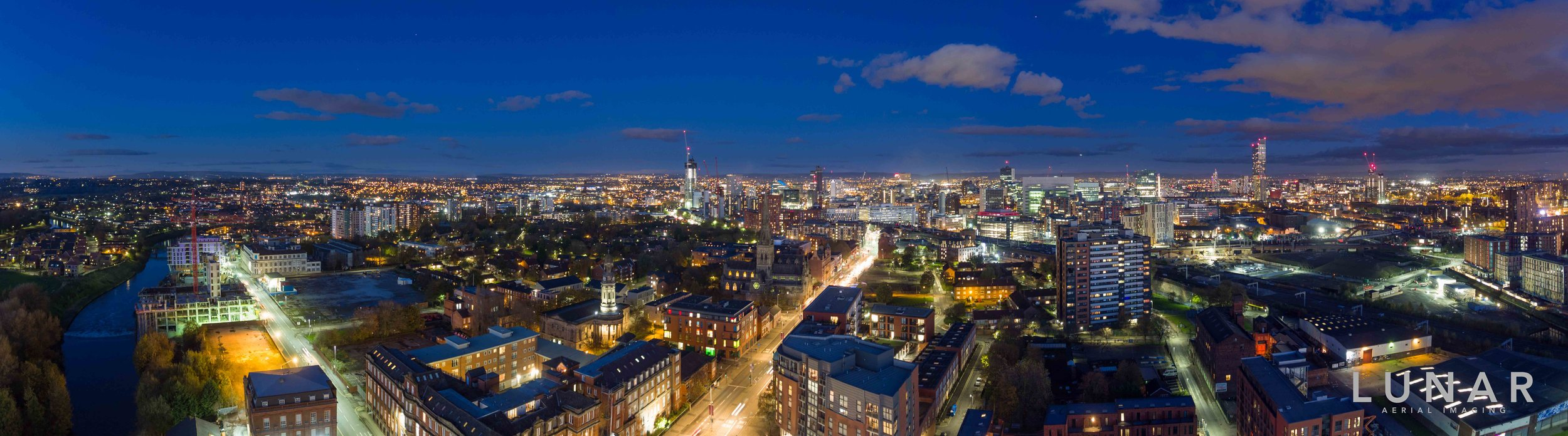 Wide aerial photo of Manchester skyline at night