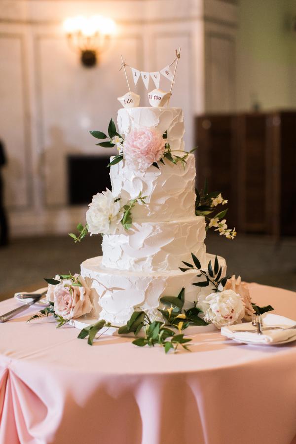 blush and white flowers on wedding cake