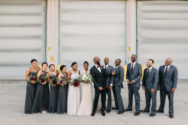wedding party photo in industrial chicago with grey suits and grey bridesmaid dresses