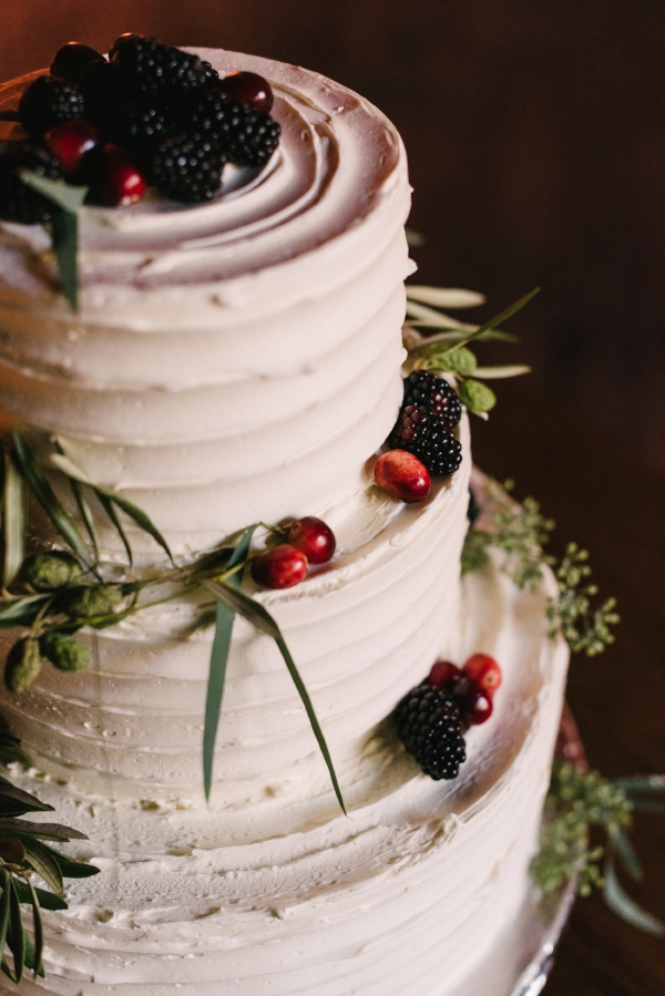 buttercream wedding cake with greenery and fresh berries