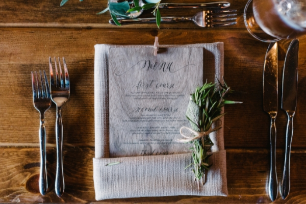 wedding place setting on farm table with wooden calligraphy menu, garaland and herb bundle by Foraged Floral