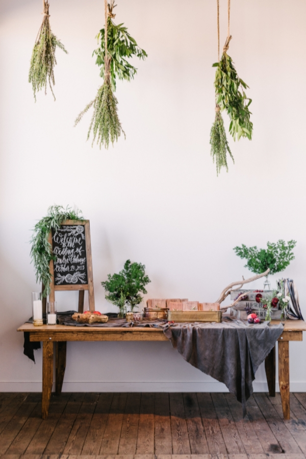 wedding welcome table design ideas with calligraphy chalkboard, greenery herb ceiling installation with burgundy and purple flowers by Foraged Floral