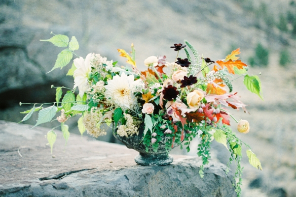 Fall flowers wedding centerpiece with peach and burgundy flowers like dahlias, garden roses, chocolate cosmos, and ranunculus by Foraged Floral at Smith Rock, Oregon