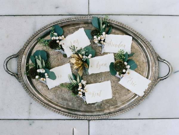 White and green wedding boutonnieres with winter textures tied with metallic ribbon and handwritten calligraphy card