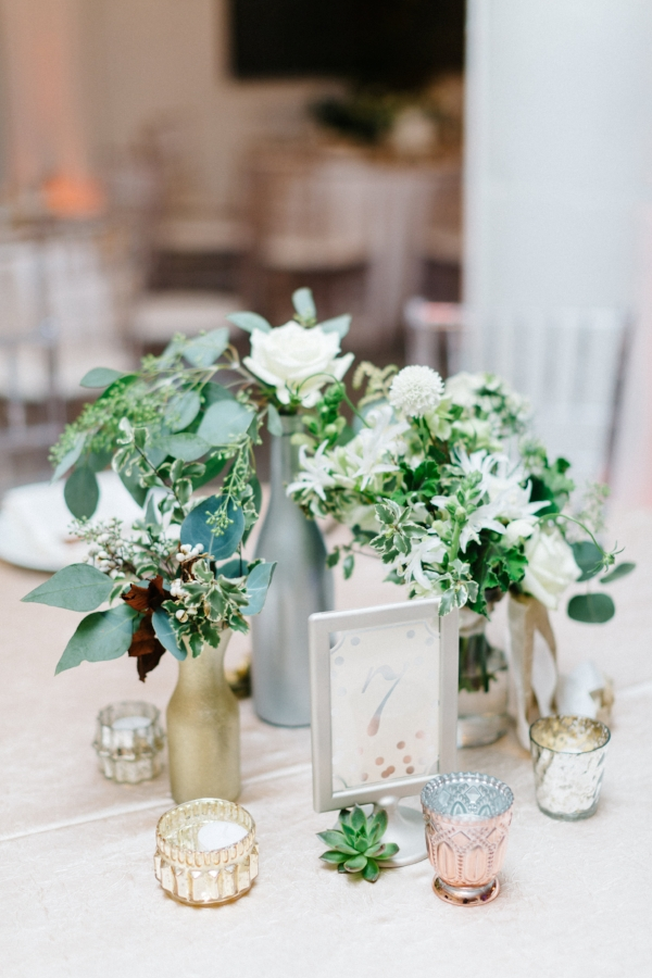 Unique wedding centerpiece made up of bud vases full of greens, and white winter flowers by Foraged Floral in Portland, Oregon