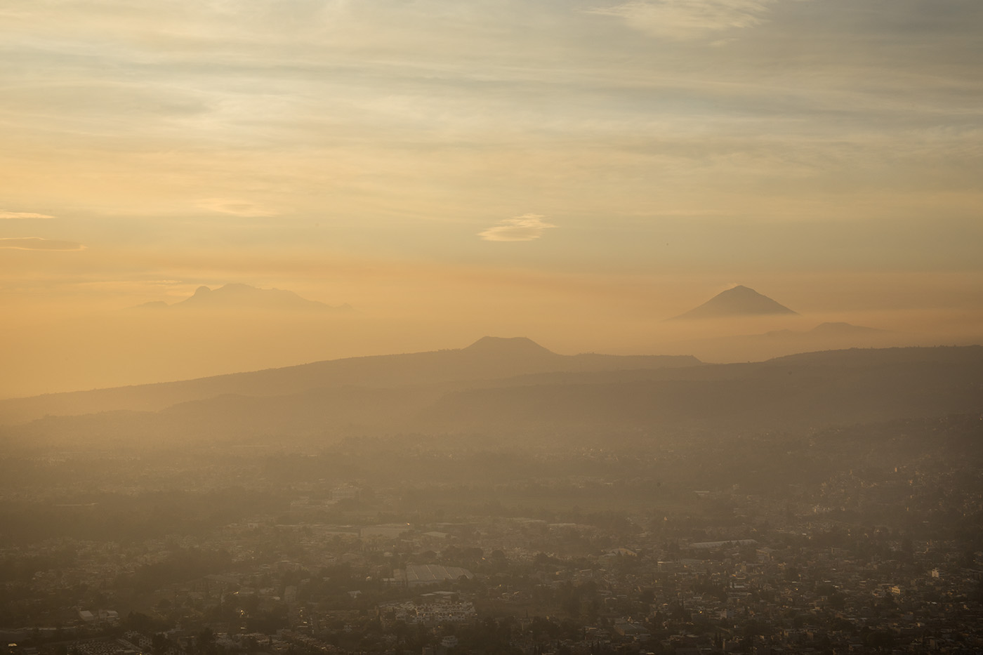 Iztaccihuatl, Popocatepetl and Teuhtli volcanos from the top of the Xochitepec during sunrise.