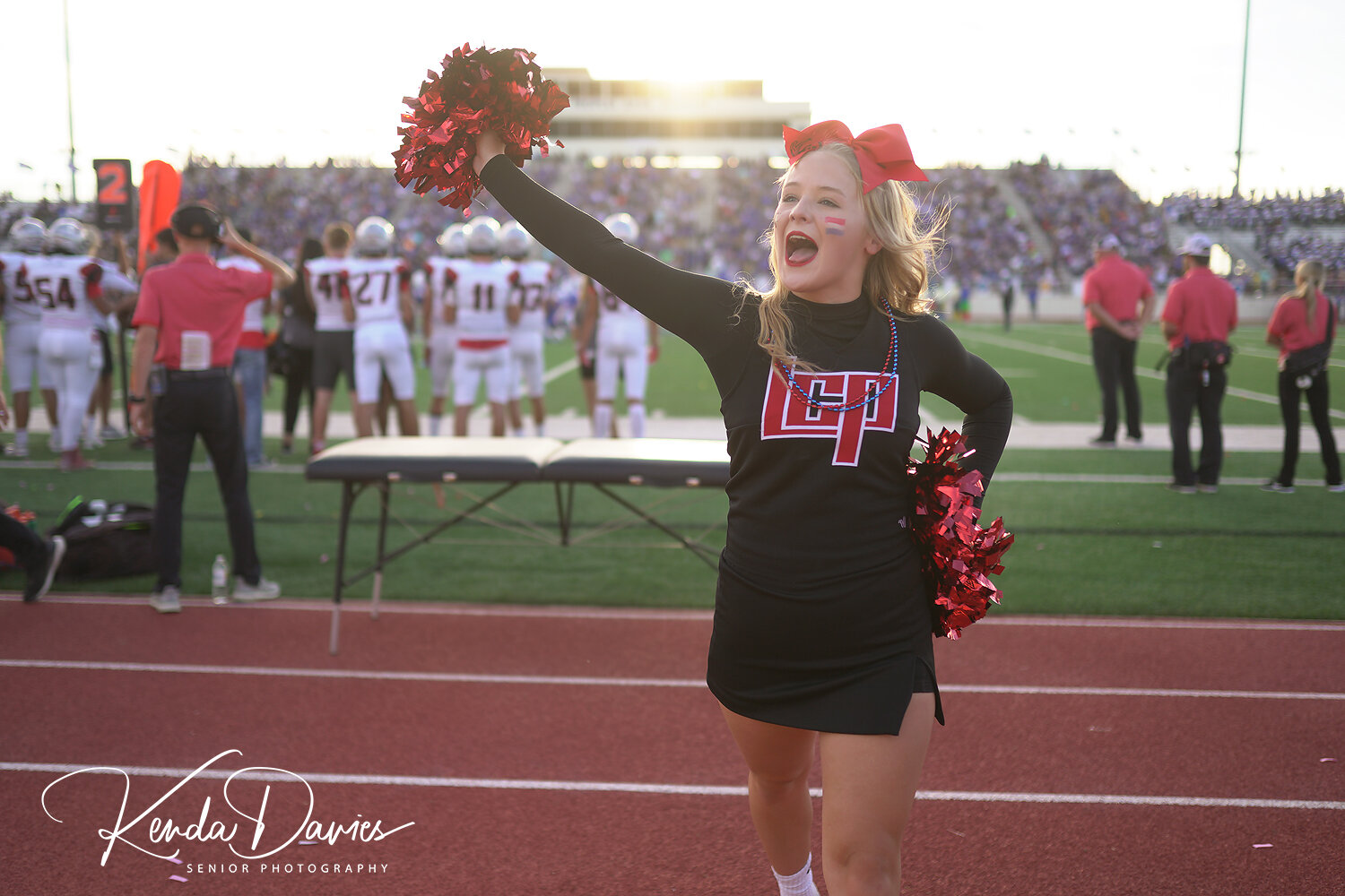 Cami Townsend yells out a cheer as Pirate football players and coaches intensely watch the game from the sidelines.