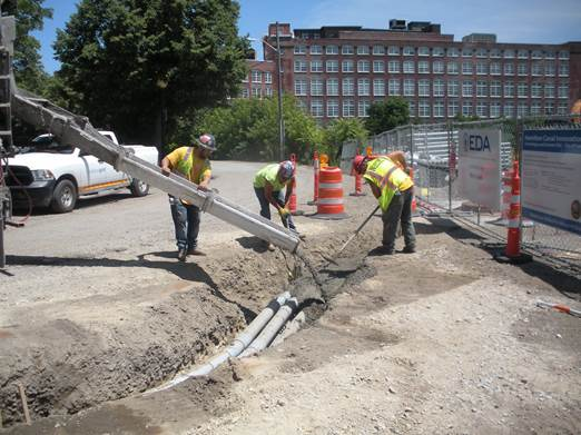 Contractor installing new concrete-incased electrical conduit