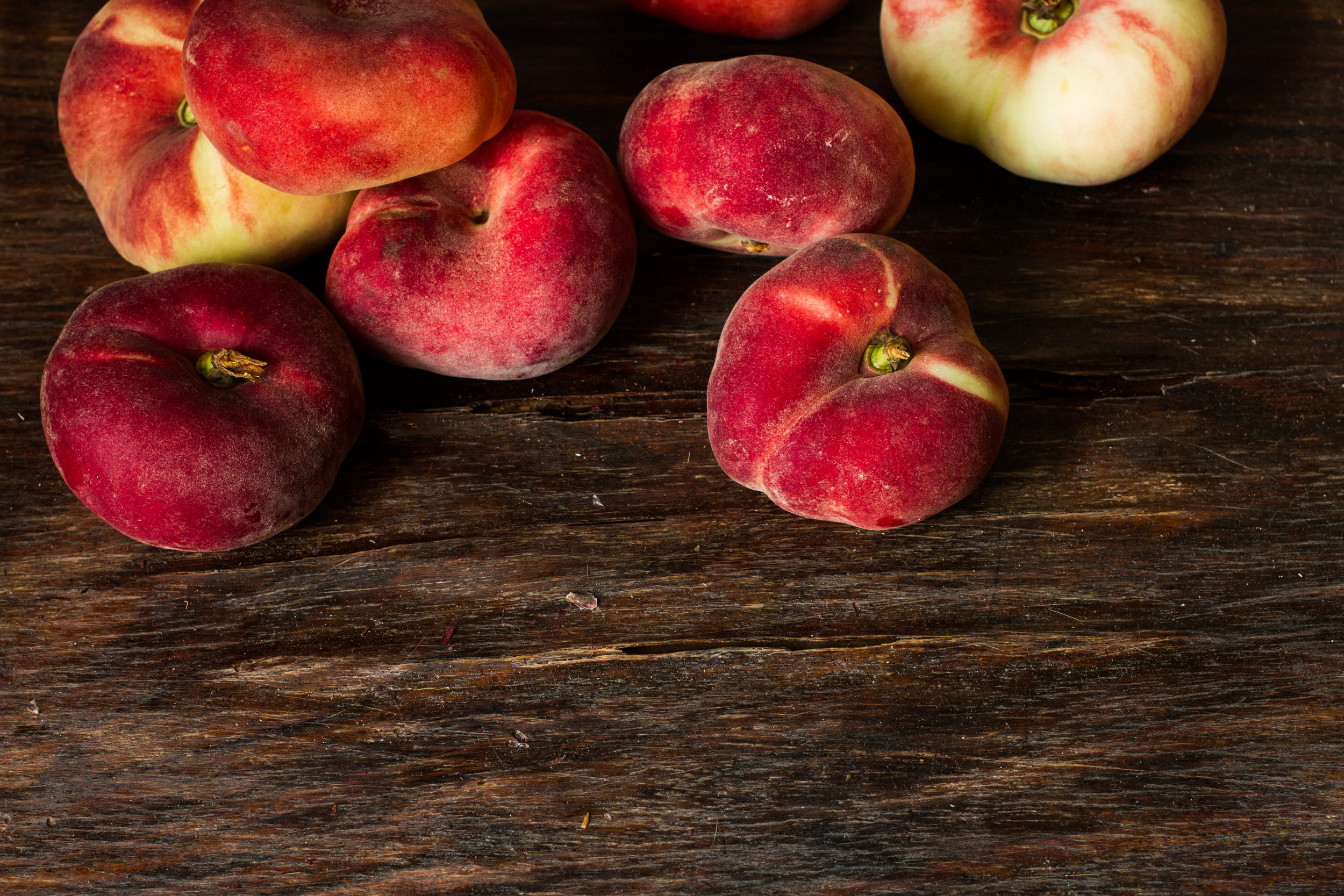 flat-ripe-peach-and-the-usual-peach-on-a-wooden-background-484613428_5184x3456.jpeg