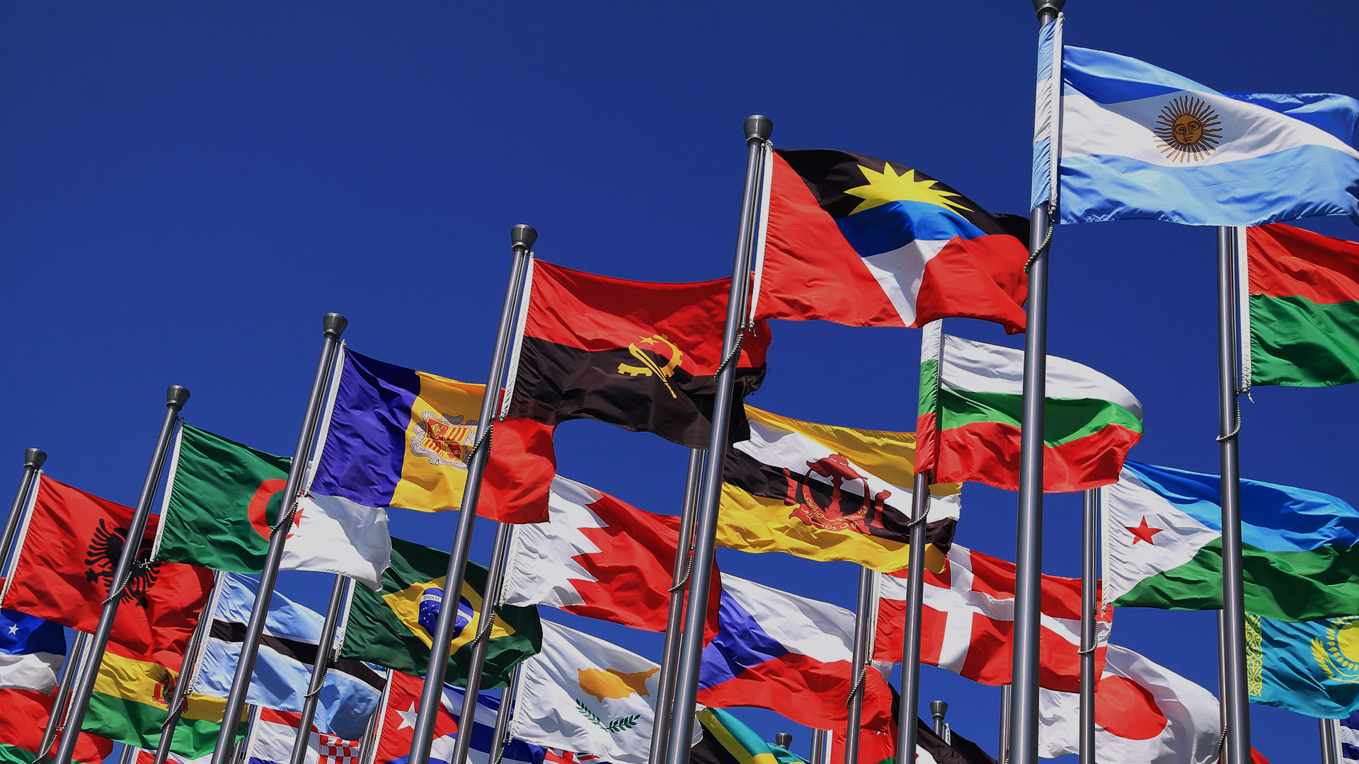 International flags of multiple nations outdoors in the blue sky