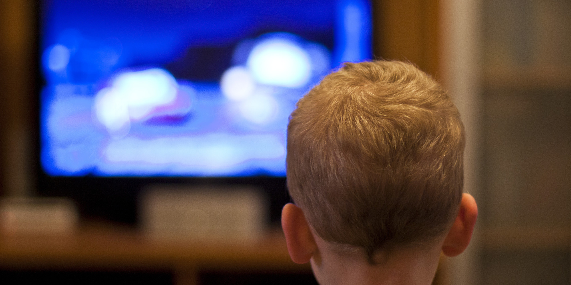 Kid with red hair watching a TV blurred in the background