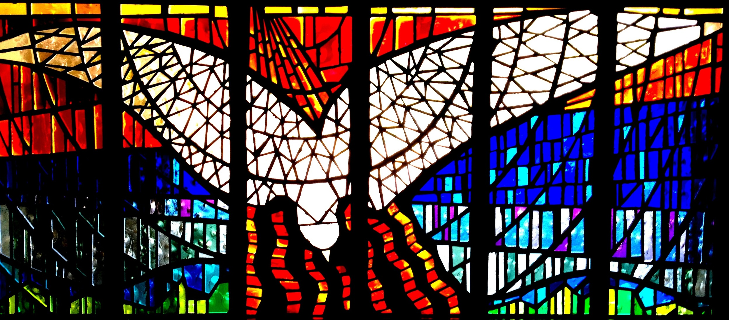 Holy Spirit dove stained glass with the vibrant colors: red, blue, yellow, green, and white.