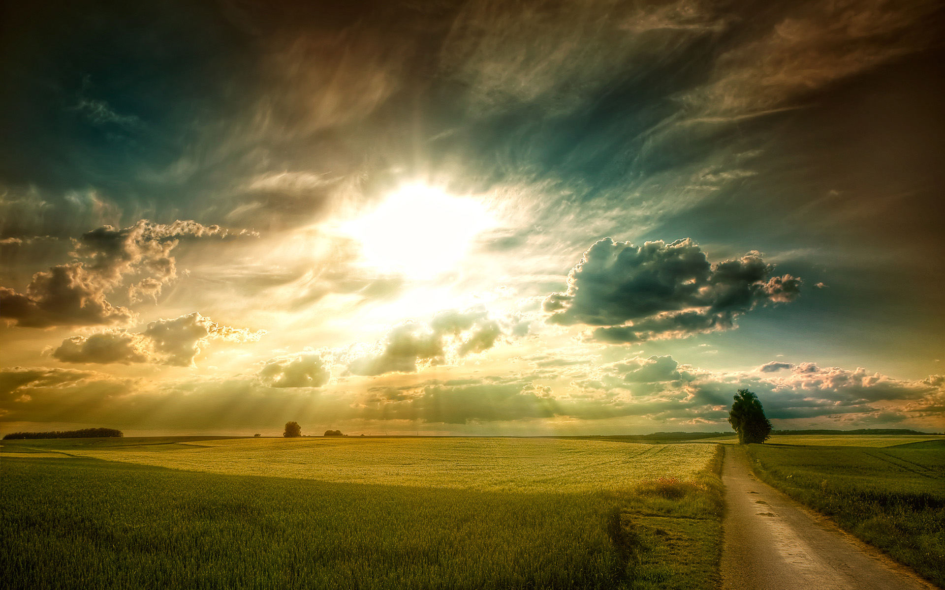 powerful sunlight coming through the clouds in a grassy field with a road nearby