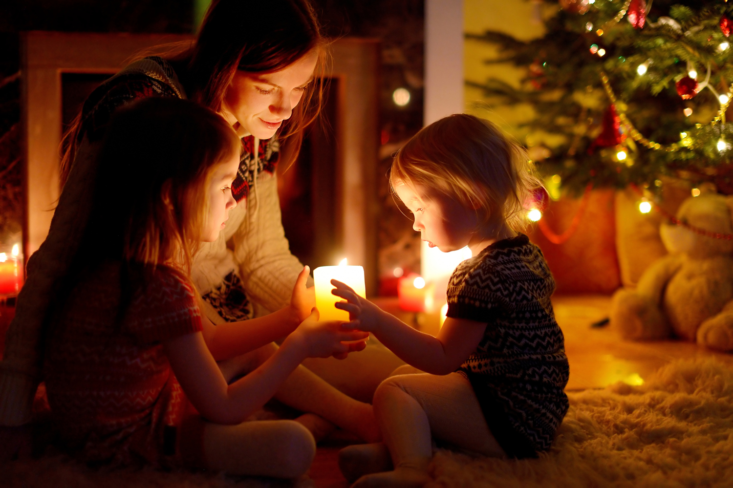 Family tradition of a little girl with her mother and sister lighting a candle underneath a Christmas Tree