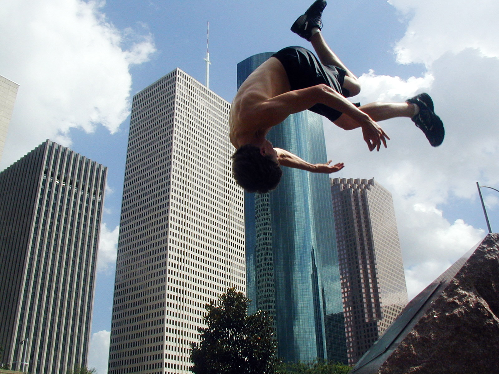 Man doing a shirtless front flip in front of a skyline on a clear day