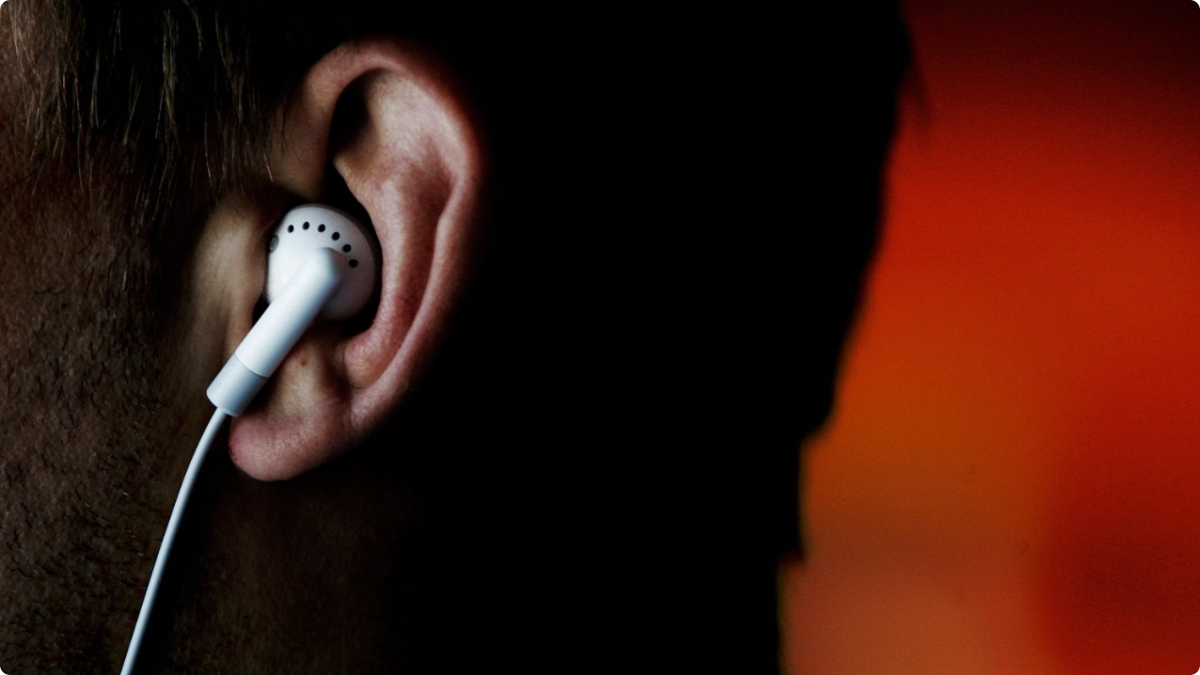 a bearded man listens to music with an earbud, profile perspective